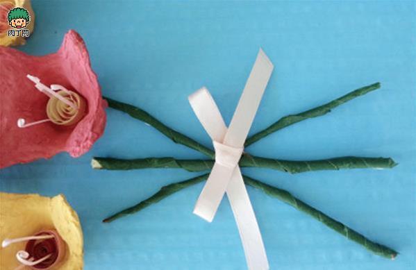 这么艳丽的花,其实是废物利用。 让我们先来看下都需要什么材料。 材料:纸质鸡蛋托、纸板、彩纸、丝带、绿色胶带(没有也可以)、树枝、广告色或水粉颜料、剪刀、裁纸刀、毛笔、白胶(乳胶)。  先用裁纸刀把鸡蛋托的一列裁下。 *蛋托的材质一般都不是太均匀,切割的时候要多加注意安全。 *这里用的是鸡蛋托的背面,相比正面,背面有弧度且粗糙,做出的成品质感会比较好。  从切下的一列中,再切下其中的一个位置。  用剪刀将蛋托的四角修成圆角,并去除毛刺,小花的雏形就已经完成了。  按照上面的方法,修整出七、八朵小花。